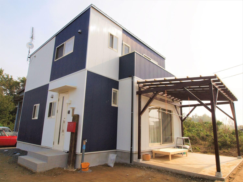 白と紺のキューブ型二階建ての外観斜め|行方市の注文住宅,ログハウスのような低価格住宅を建てるならエイ・ワン